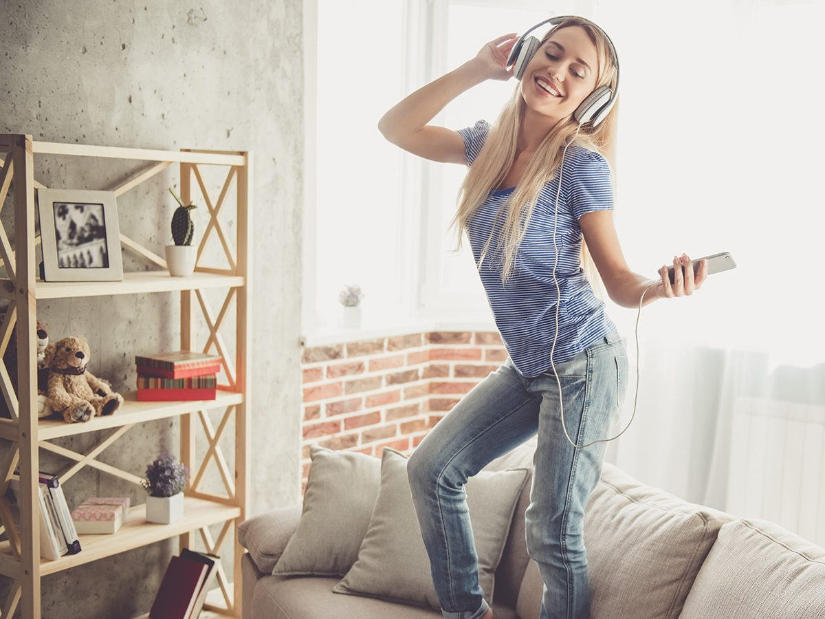 Rainy mood, woman listening to music and dancing on couch