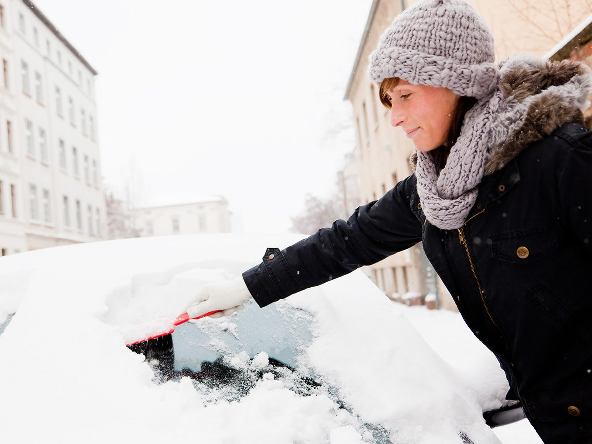 Rainy mood, woman scraping snow off a car