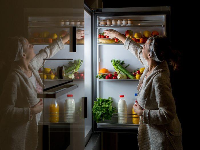 Weight Los Myths woman snacking at fridge late at night