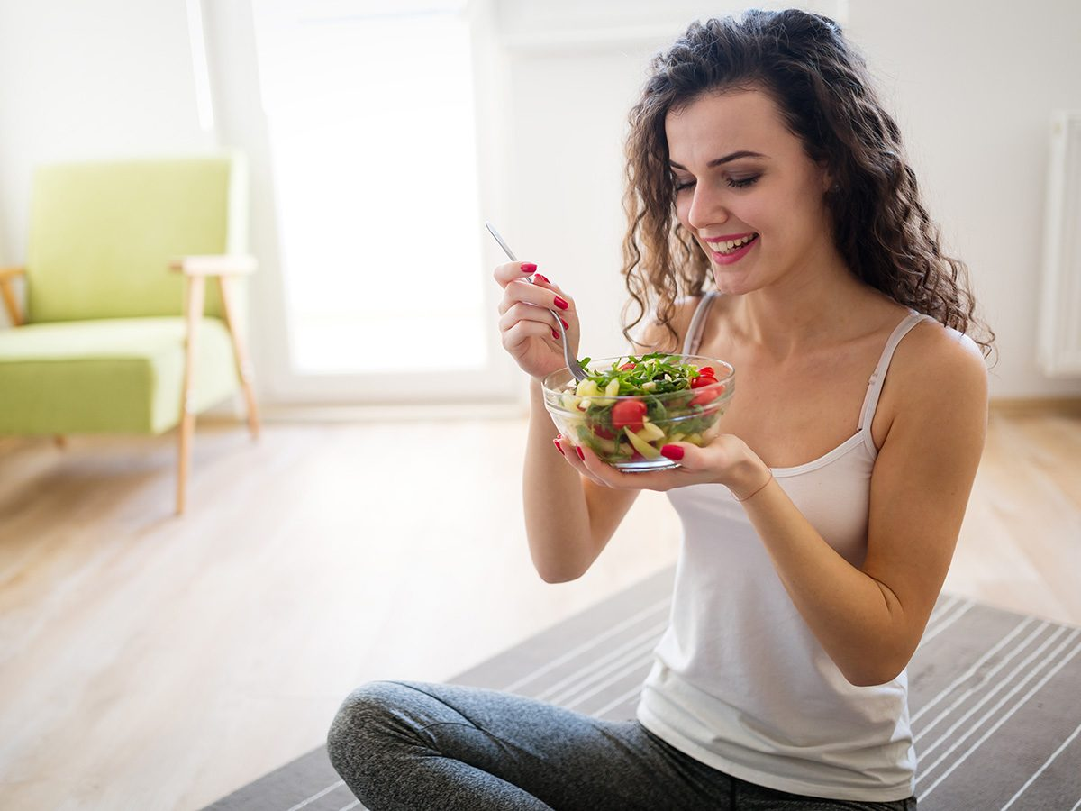 Weight loss myths, woman on yoga mat eating salad