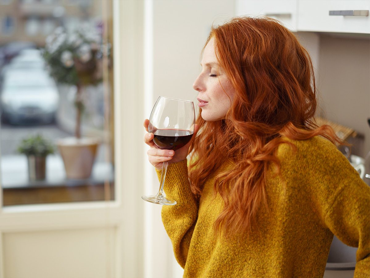 Redhead woman sniffing glass of wine in kitchen