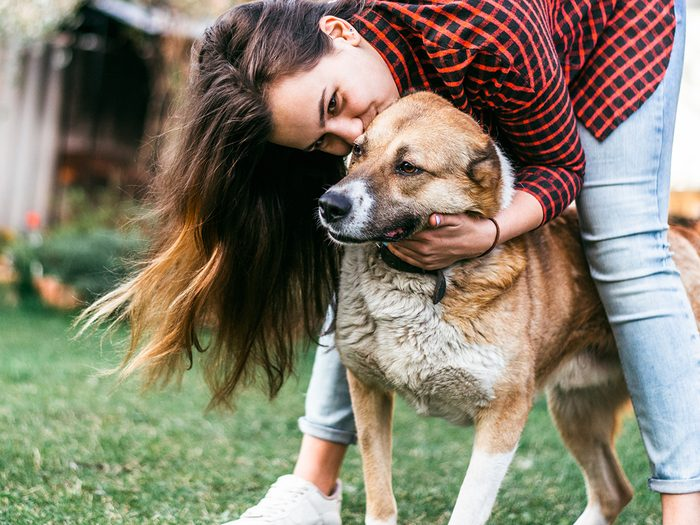 Happiness, young woman hugging a scruffy dog outdoors