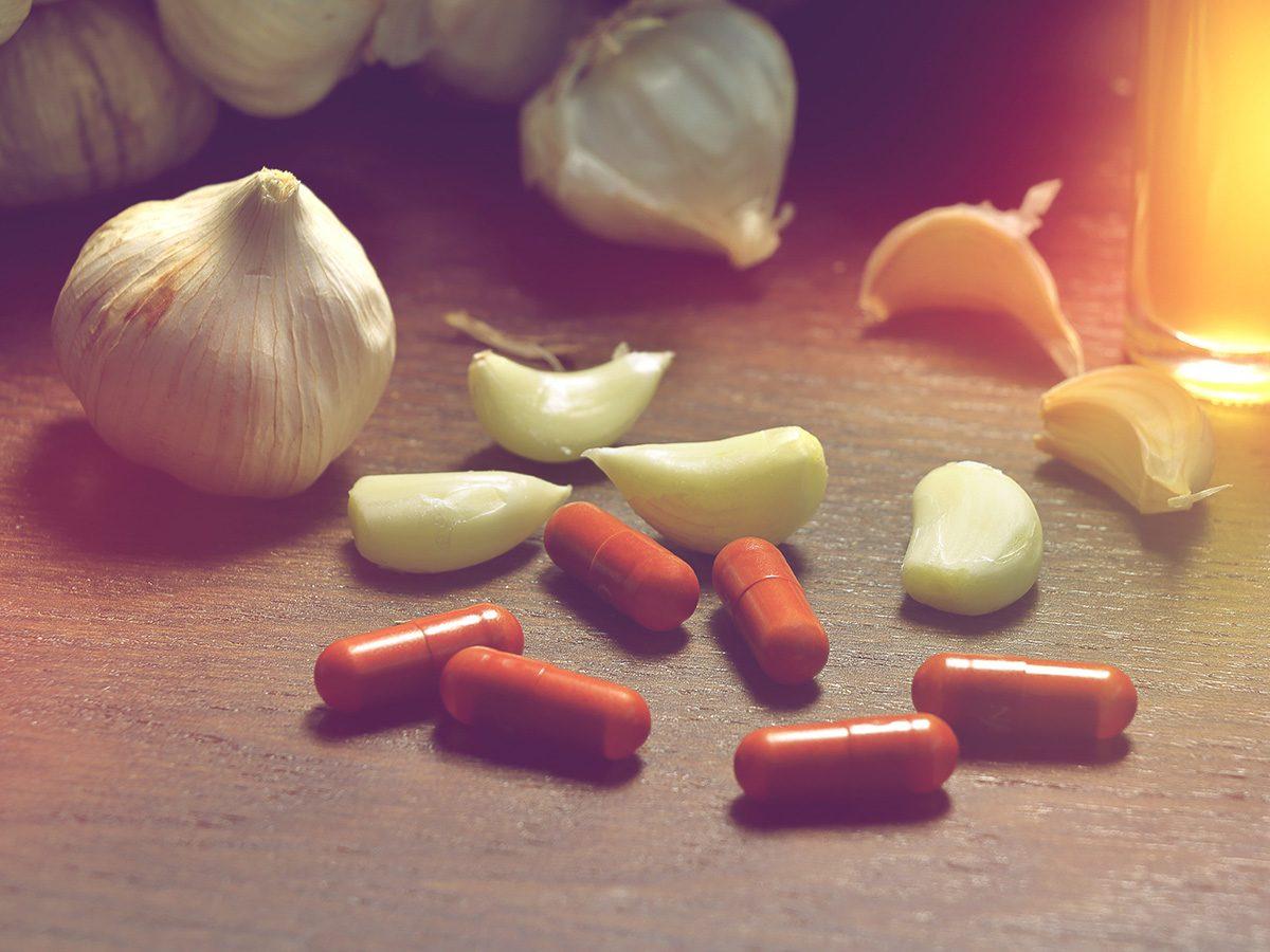 Biotin, garlic pills lying next to fresh garlic