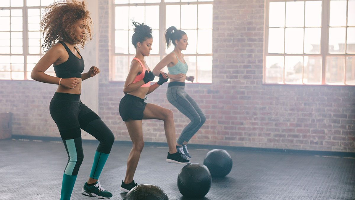 Fitness tips, women workout out together with weighted balls