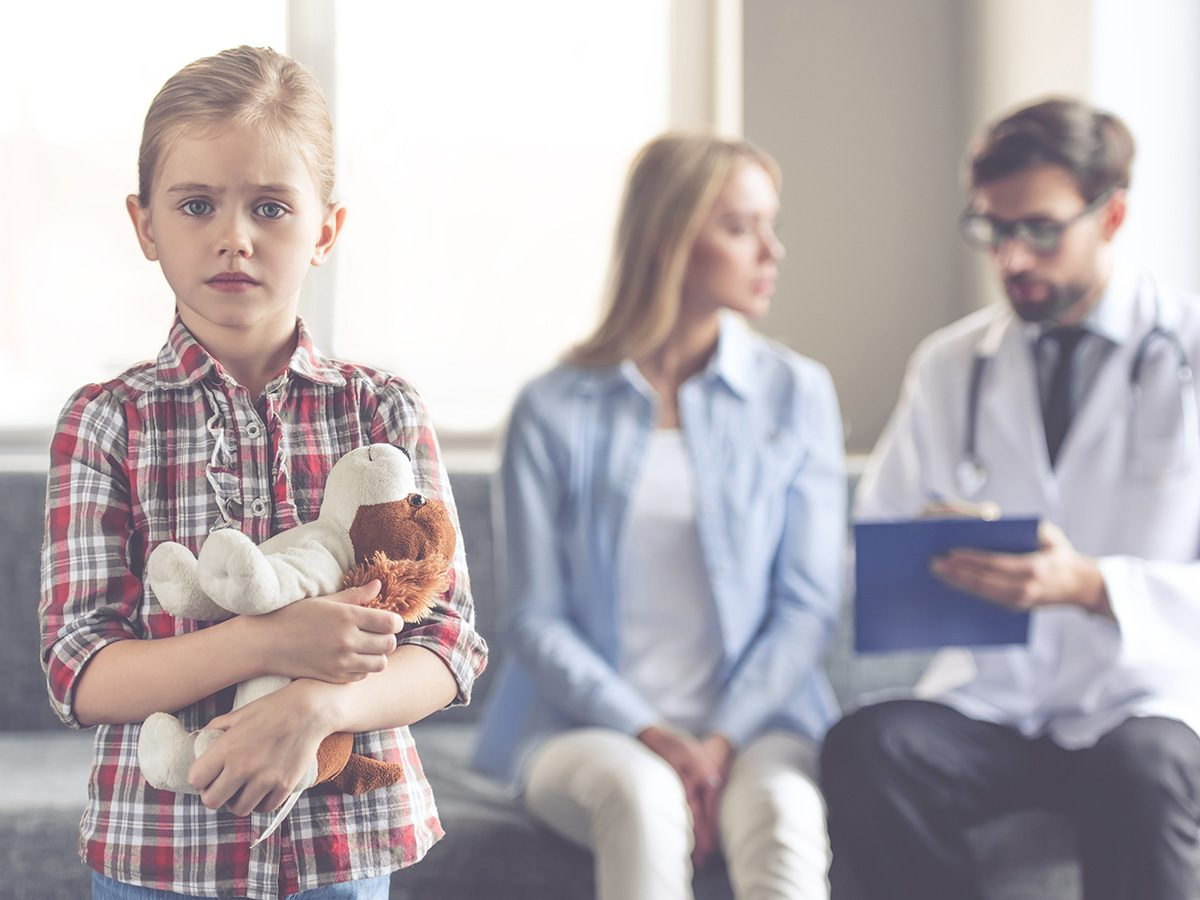 Dying, worried young girl holds her teddy bear as her mom talks to a doctor