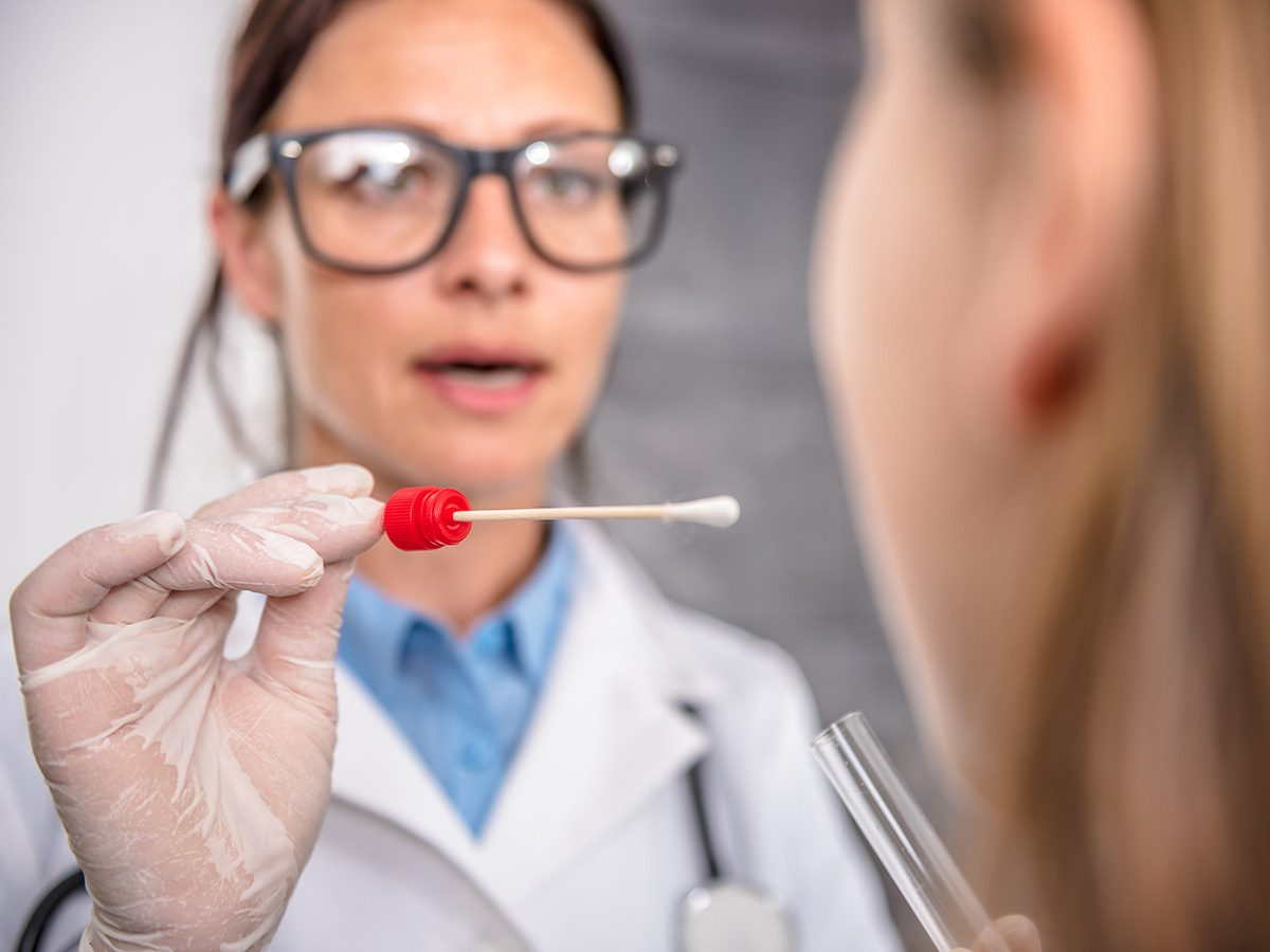 Genetic testing, Doctor swabs woman's mouth