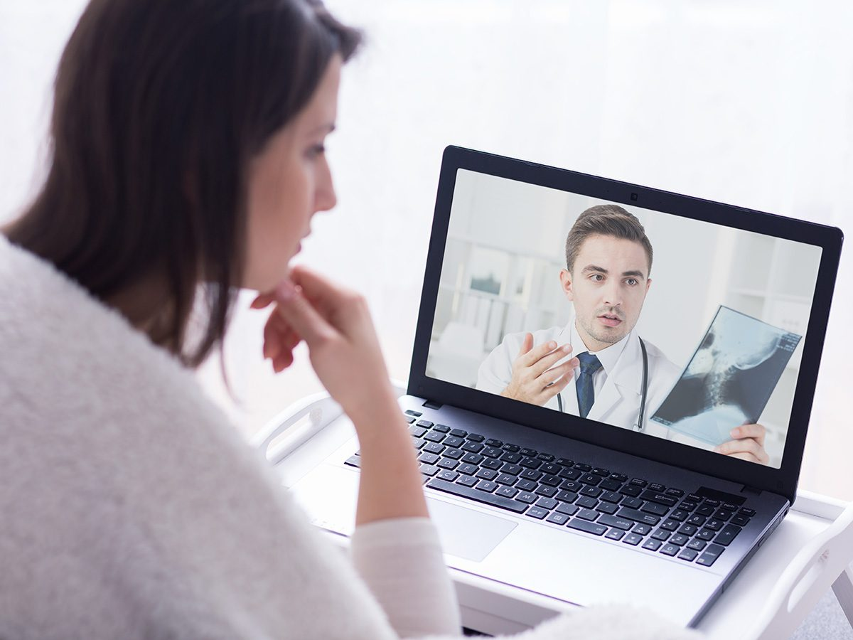 Genetic testing, Woman speaks to her doctor from home via computer