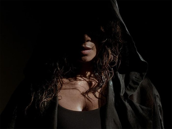 Halle Berry stands in shadow with a boxing robe hood partially covering her face
