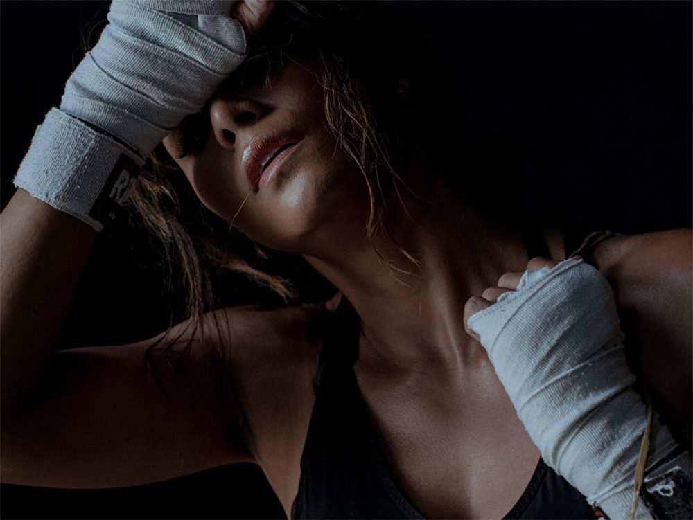 Halle Berry wipes her sweaty forehead with her hands in boxing wraps
