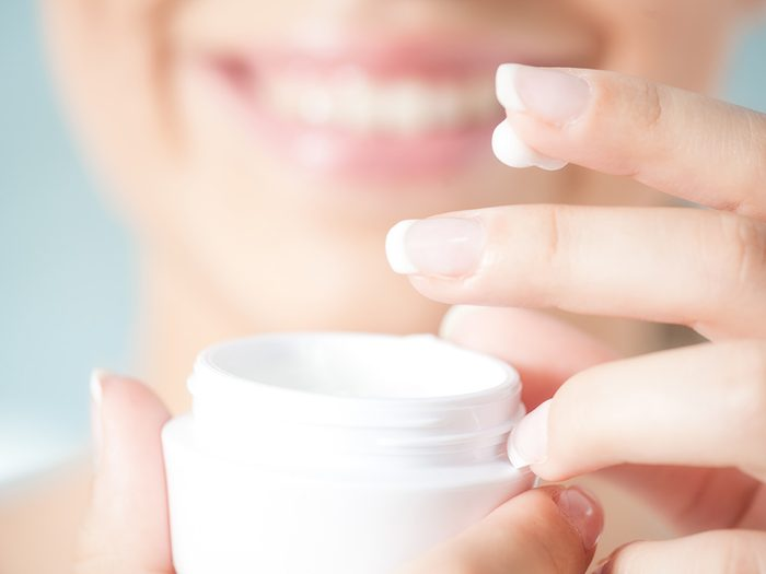 Health trends, a woman dipping her fingers into a jar of face cream