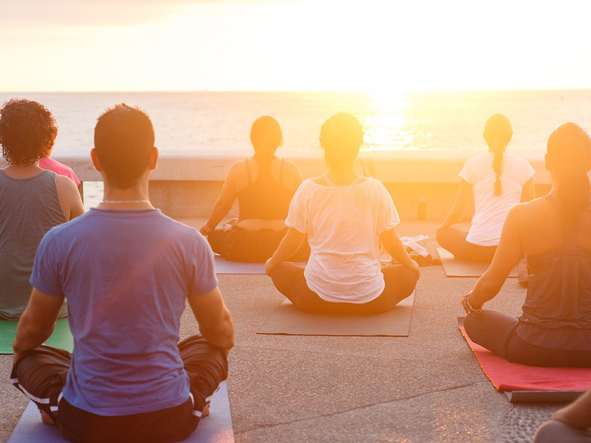 Health trends, sunrise yoga on a pier