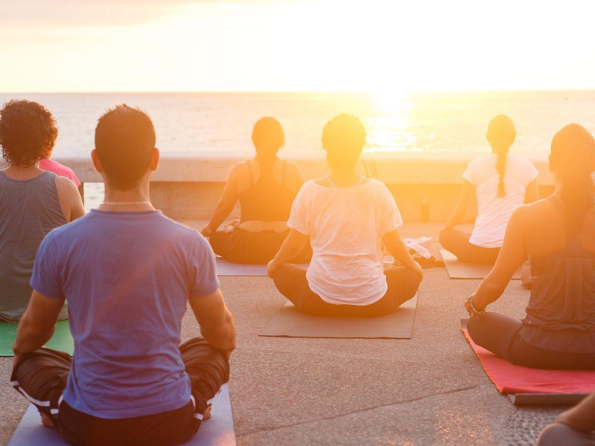 Health trends, sunrise yoga on a pier