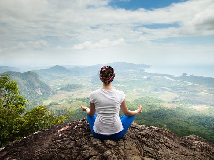 Health trends, woman doing yoga on top of a mountain in Thailand
