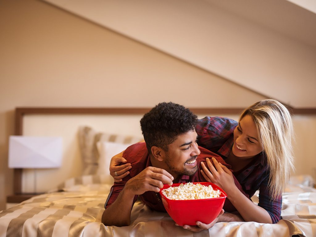 Healthy snacks, couple lying on bed eating popcorn