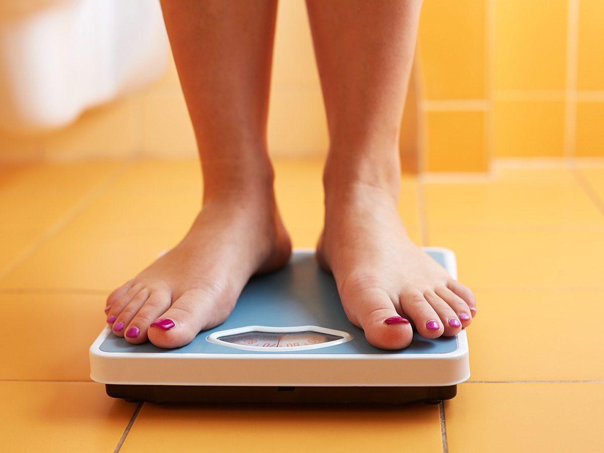 Health snacks, woman standing on scale to weigh herself