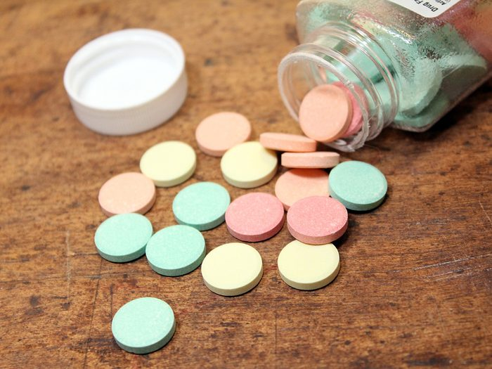 Antacid pills for hearburn spilled out on a wood table