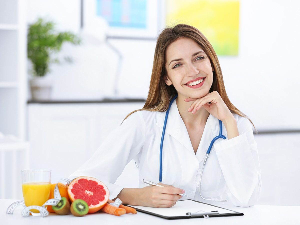 A nutritionist next to a bunch a fruit ready to council on heartburn