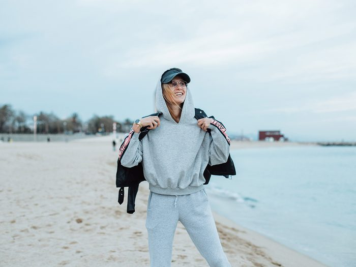 Woman standing on beach in sweat pants and sweat shirt because she has heartburn