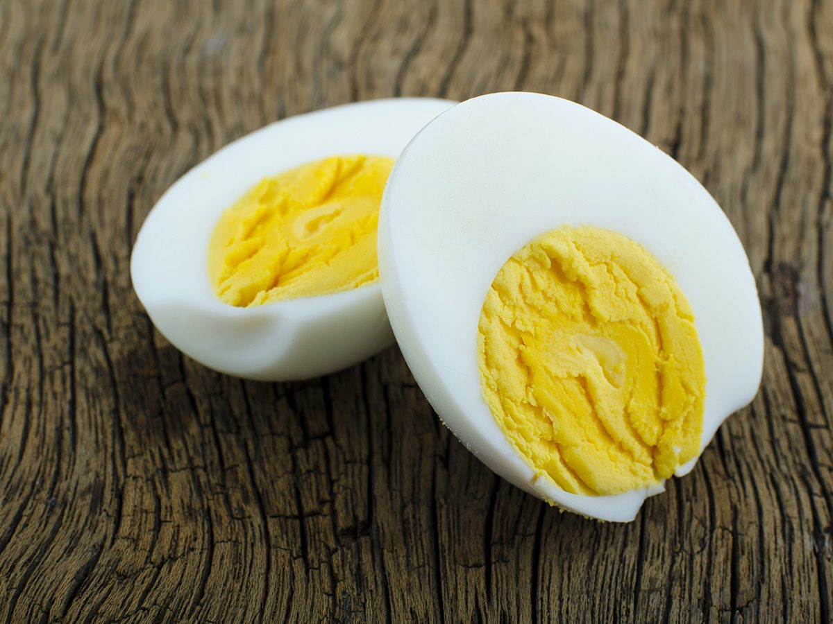 How to eat healthy, hardboiled egg cut in half on a wooden surface