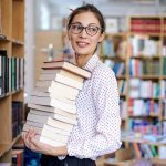 Intelligence, woman in library holding stack of books