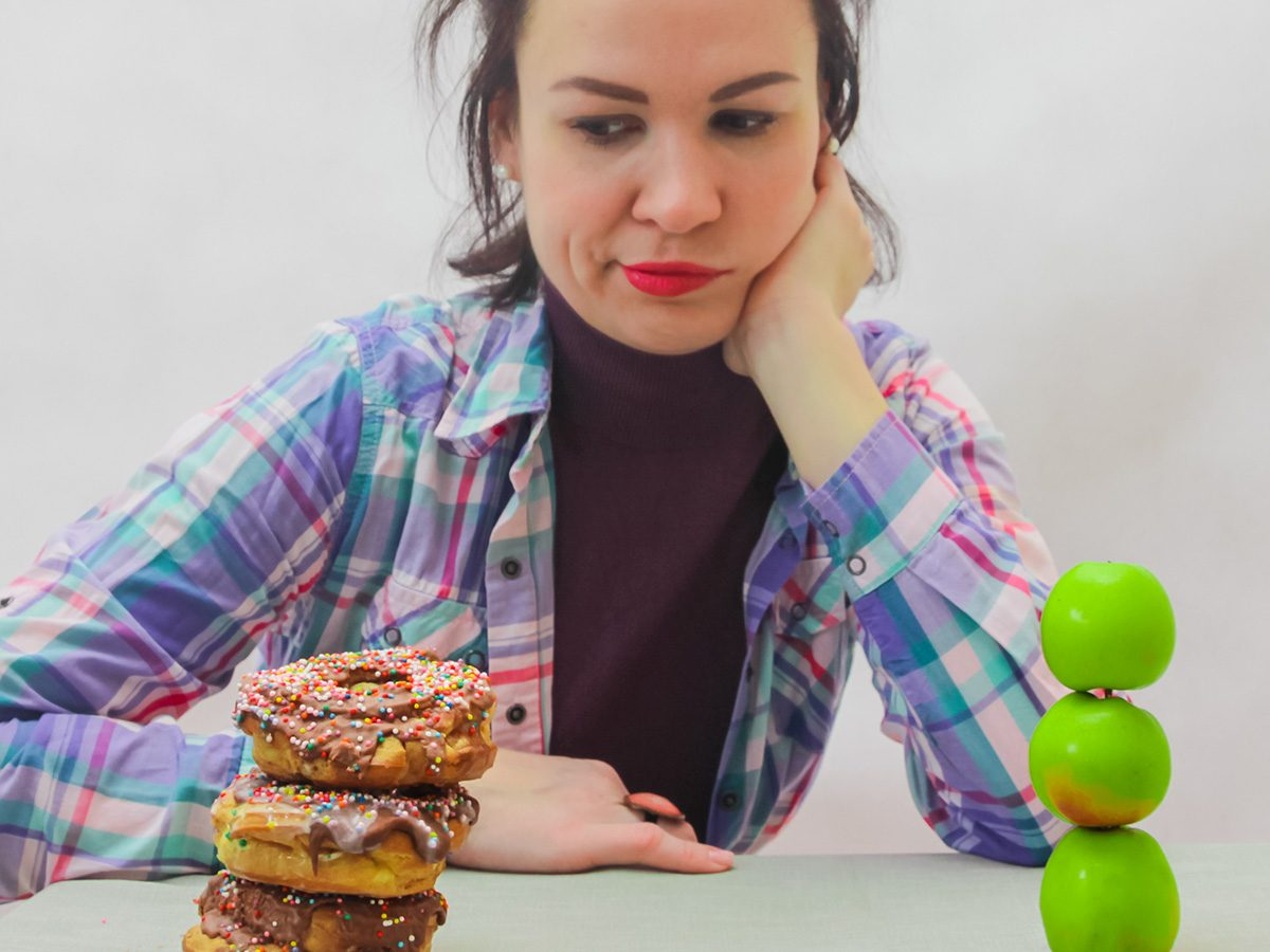 Intellience, woman trying to decide between donuts and fruit