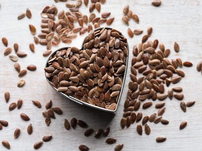 Menopause symptoms, flaxseed spilling out a heart-shaped container