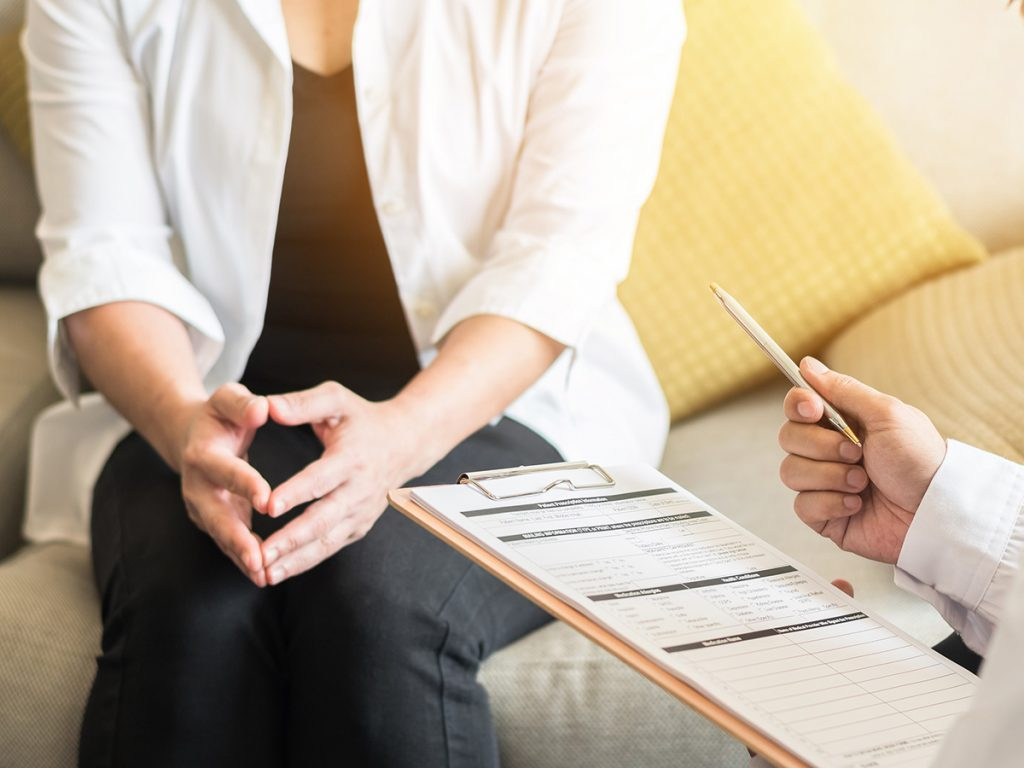 Menopause symptoms, middle-aged woman chats with her doctor