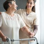 Osteoporosis, elderly woman walks in hospital with a walker