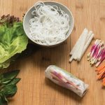 Assembling rice paper rolls with raw veggies and rice noodles