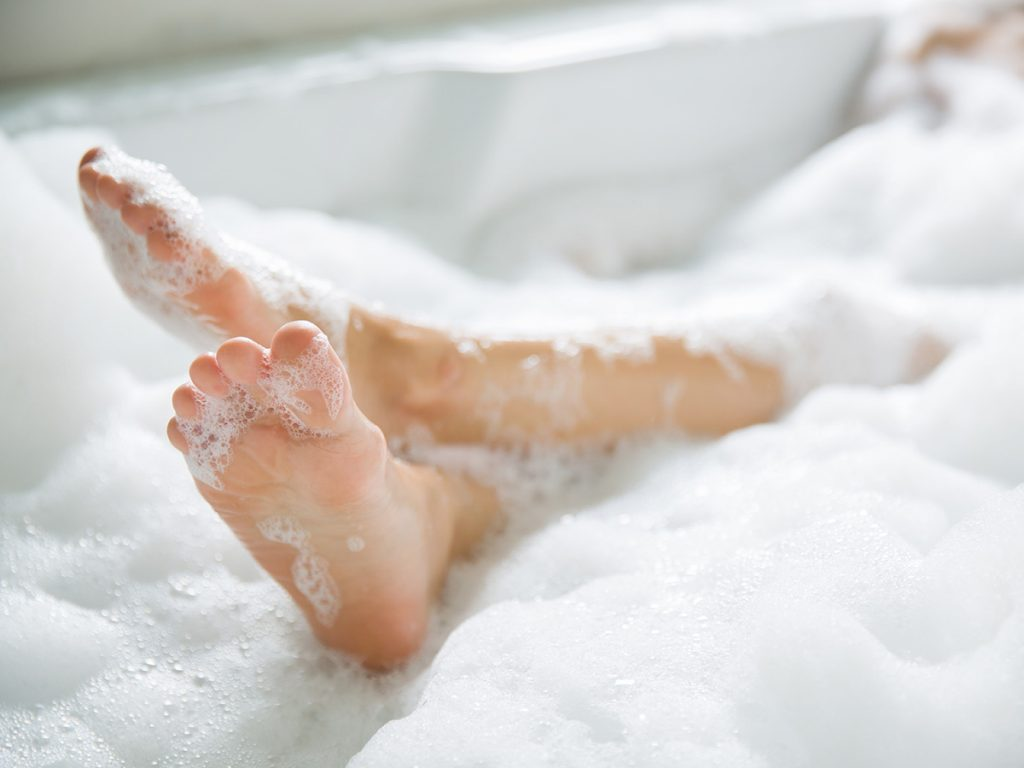 Self love, a woman's feet in a bubble bath