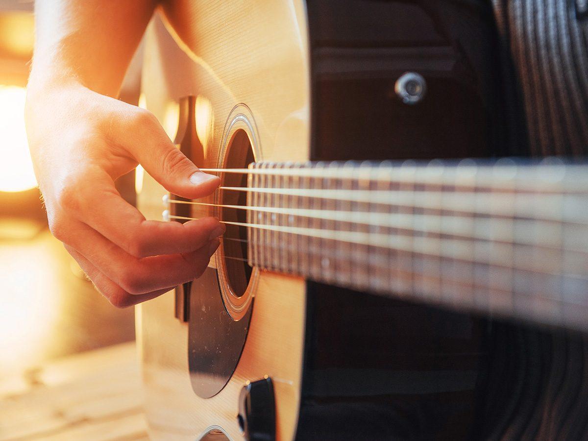 Self love, close-up of hands strumming a guitar