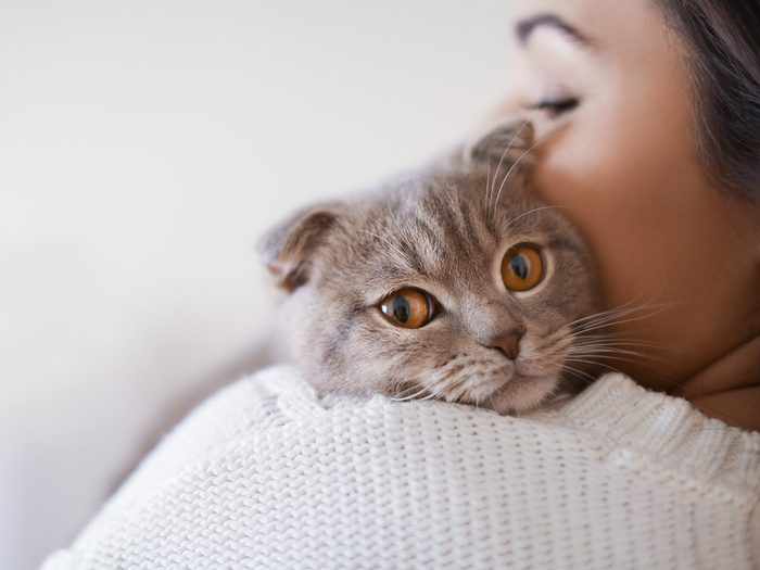 Self love, a woman hugs a kitten, whose head peeks out over her shoulder