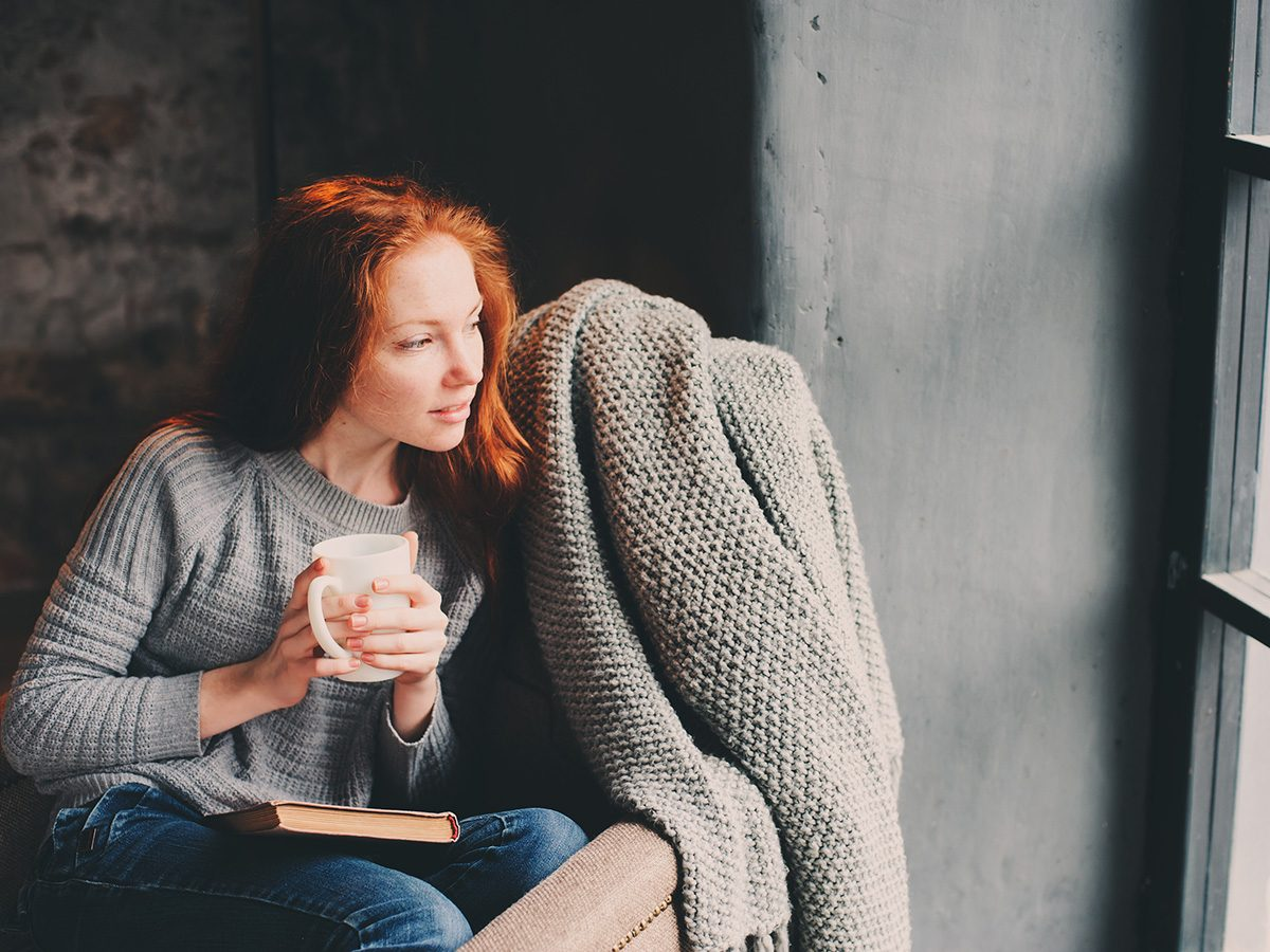 Self love, woman enjoys some alone time as she sips coffee in a comfy armchair