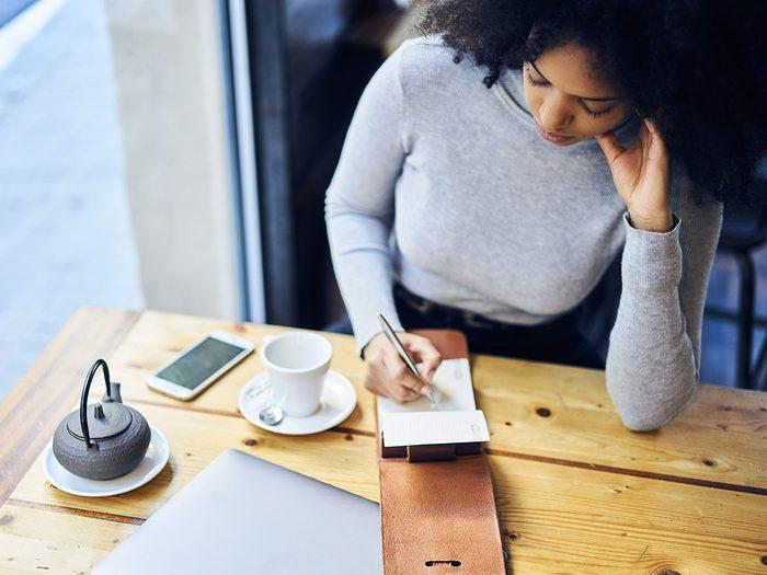 Self love, woman writes list in coffee shop as she drinks tea
