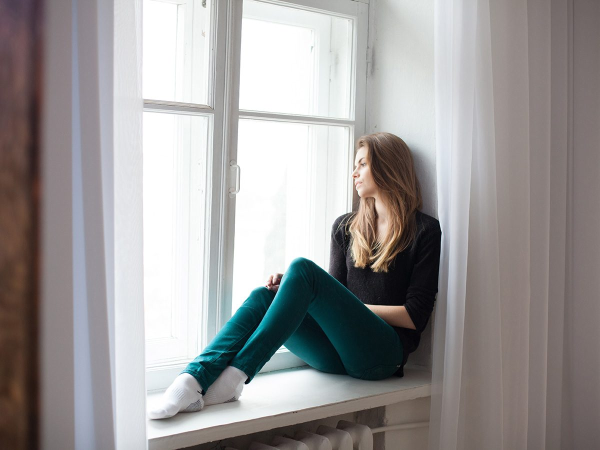 Self love, Woman sits on ledge and looks out window
