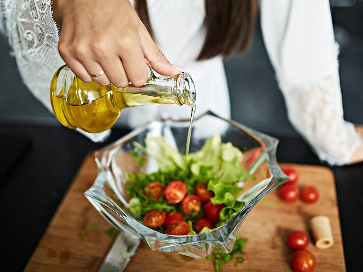 Self love, woman pours dressing on a big green salad