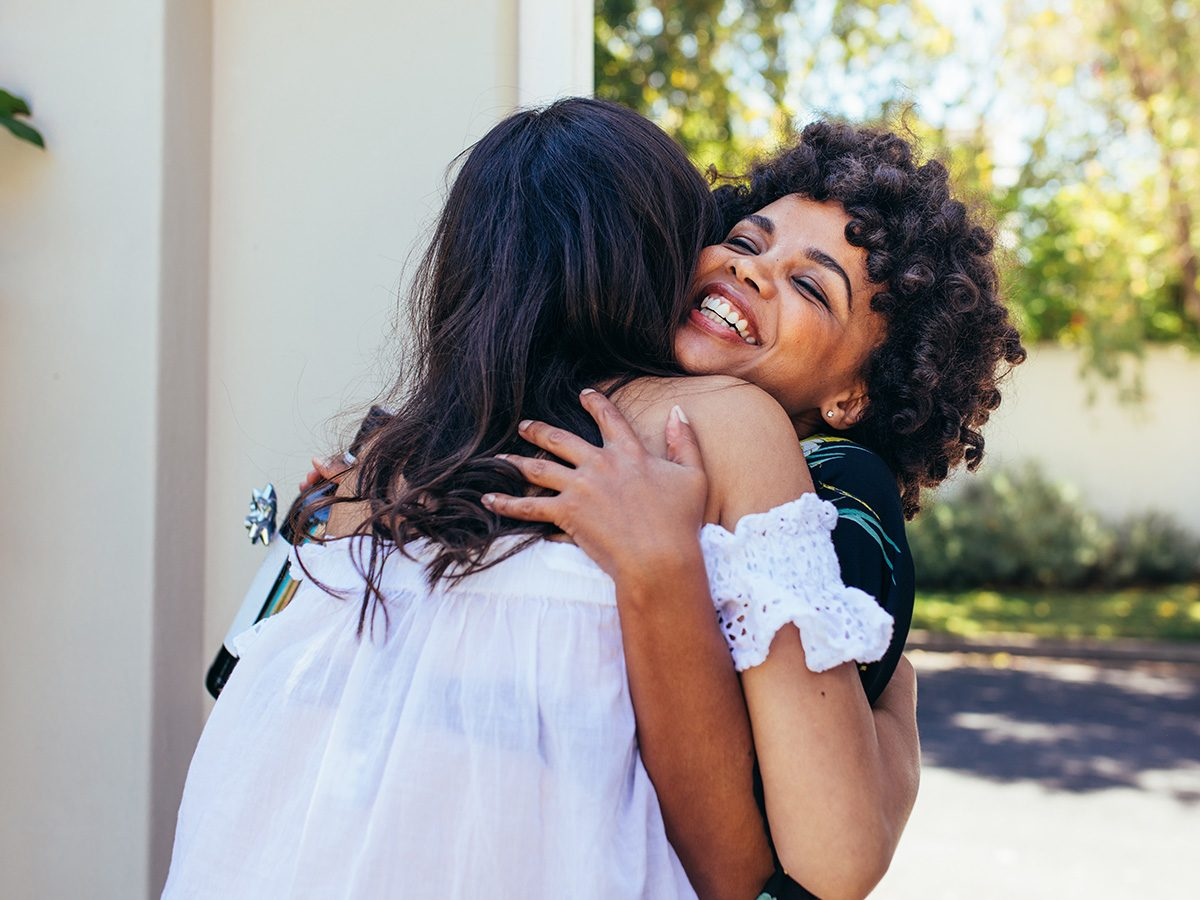 Self love, two woman hug at the entrance to a dinner party