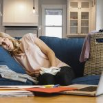 Exhausted woman sleeps sitting up on couch