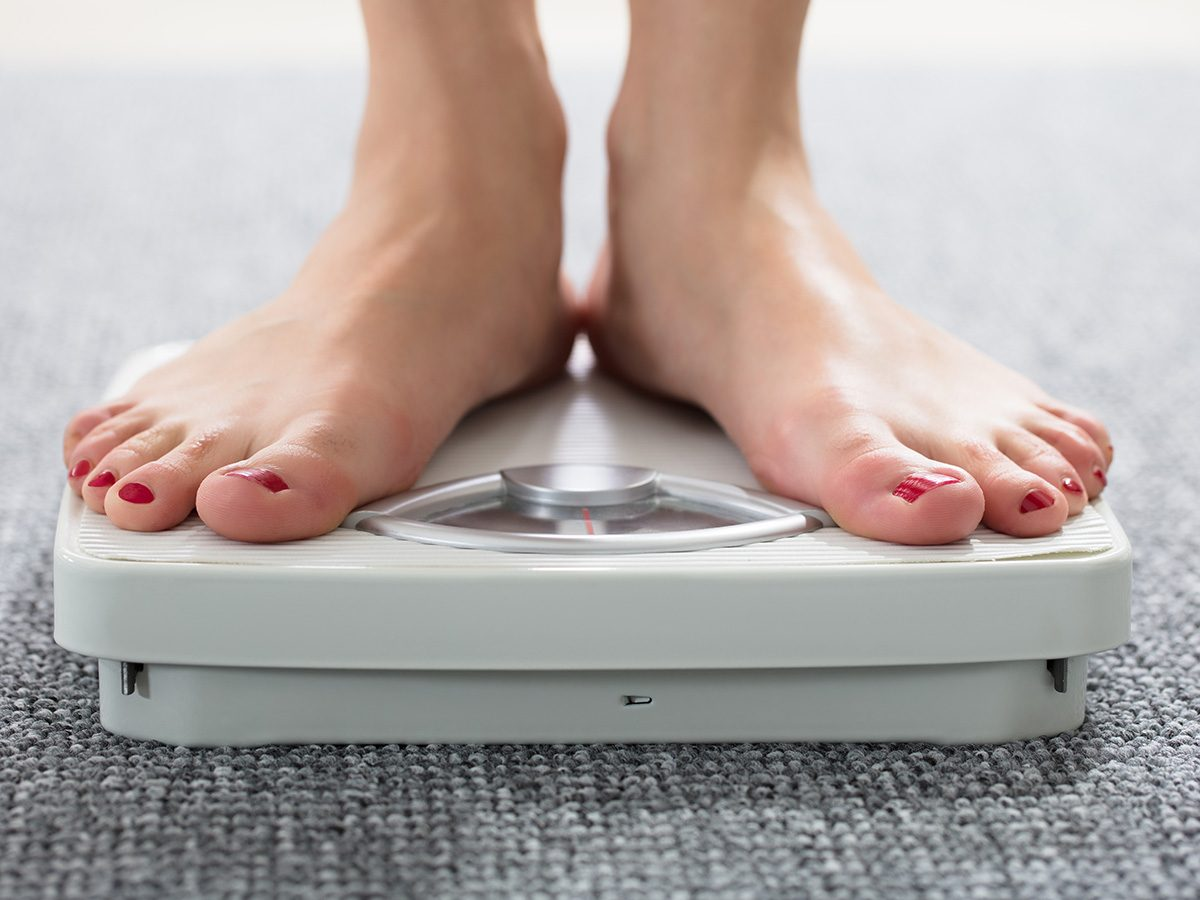 Weight gain, woman's feet on scale