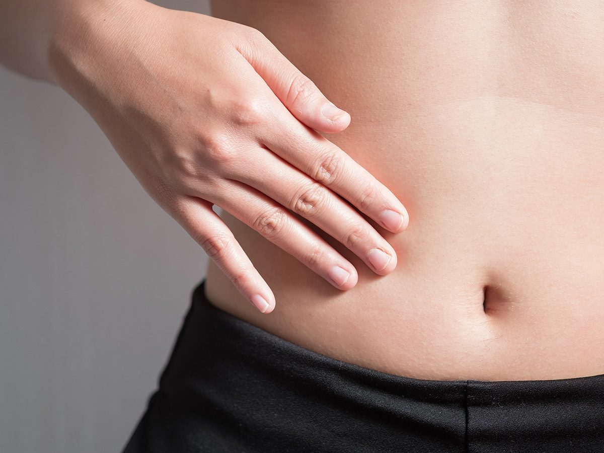 Weight gain, woman touches sore abdomen
