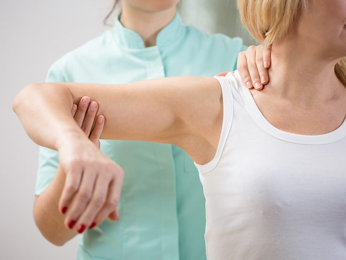 Weight gain, therapist moves woman's stiff arm and shoulder