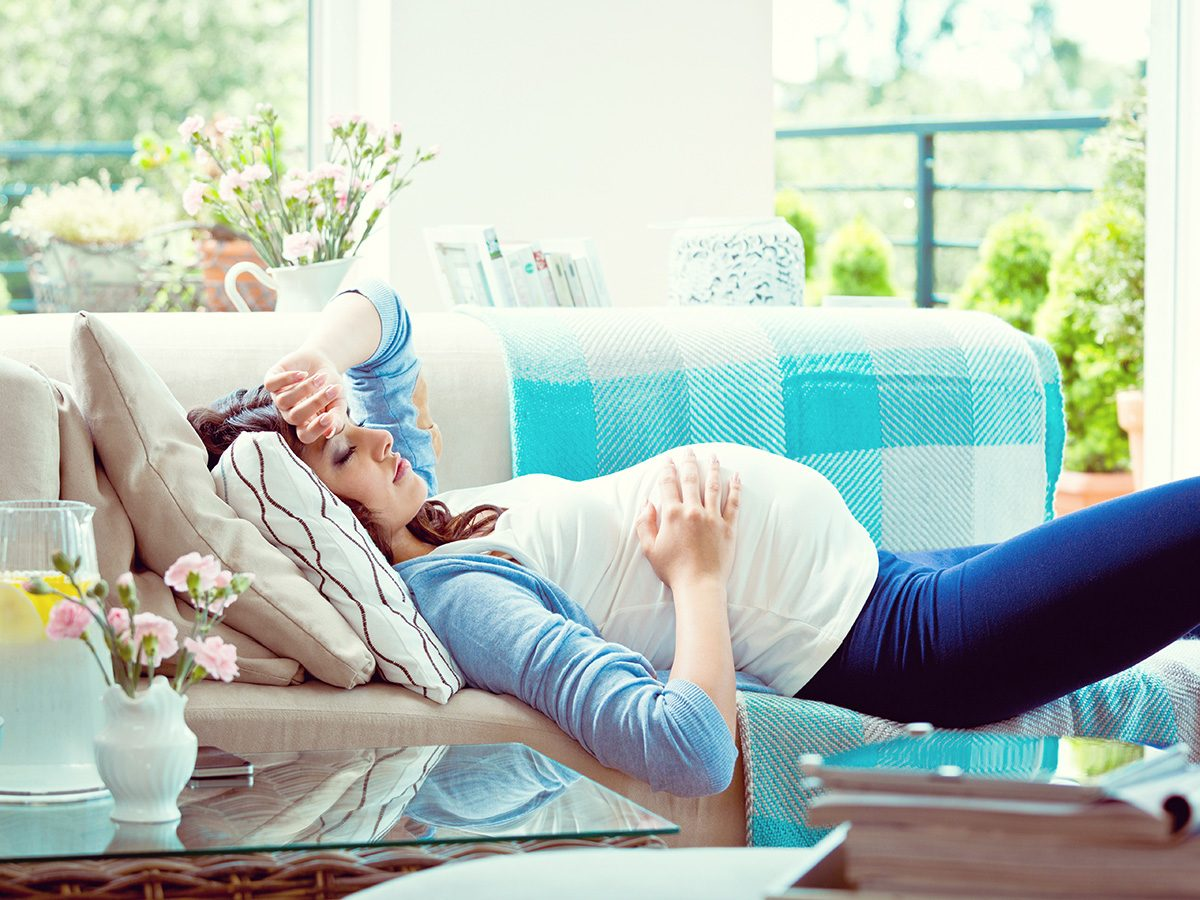 Tired pregnant woman lying on couch because she's low on iron
