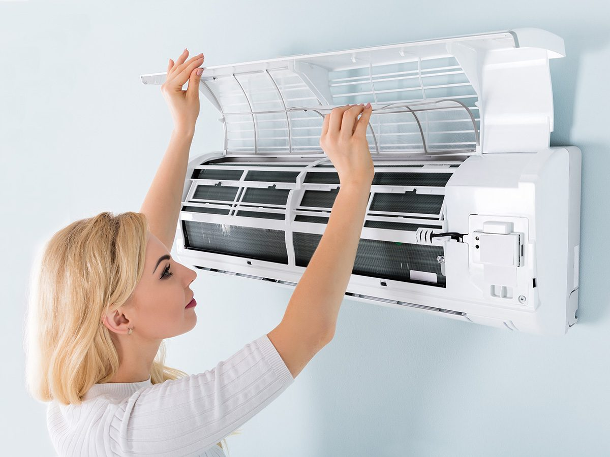 Allergies, woman changing filters for air conditioner