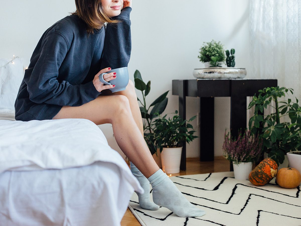 Allergies, woman sits on bed surrounded by plants