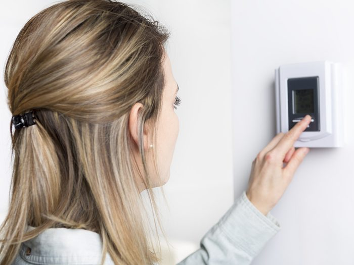 Allergies, woman adjusts thermostat