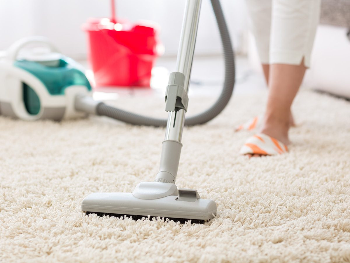 Allergies, woman vacuuming her carpet