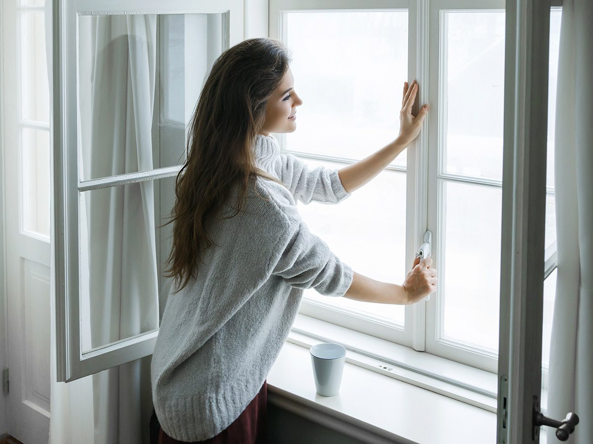 Allergies, woman closing windows of her house