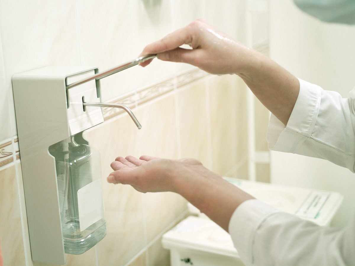 Eczema, woman applies hand sanitizer in a washroom