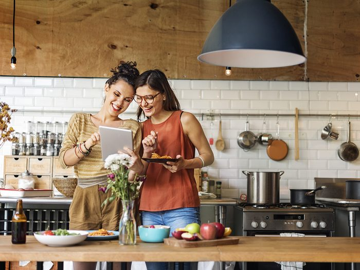 Extreme weight loss, women in kitchen looking at tablet