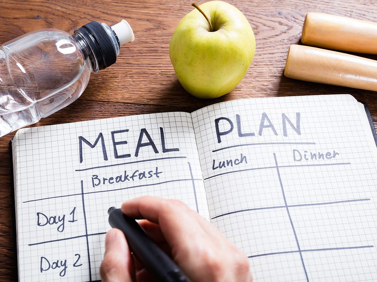 Extreme weight loss, person writes in a meal planning notebook